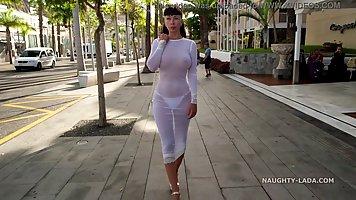 Брюнетка в полупрозрачном платье готова к жесткому соло прямо на улице
