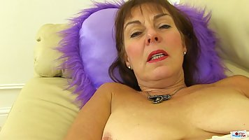 A mature lady in pantyhose lying on the couch fiddles with her pussy and gets an...