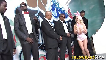 Blonde gets double penetration from a crowd of blacks with a deep blowjob