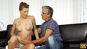 Old man on the couch fucks a young chick in a turquoise bikini
